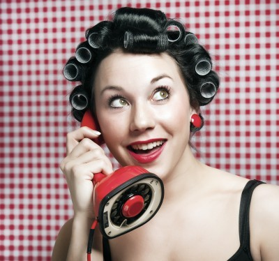 Lady wearing curlers talking on old-fashioned phone