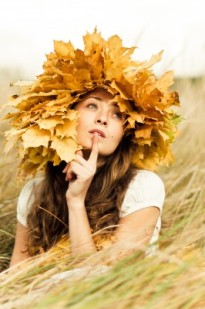 Woman looking pensive with leaves on her head