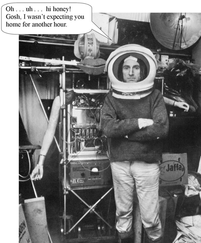 Man with helmut standing next to a robot. Linda Vernon Humor